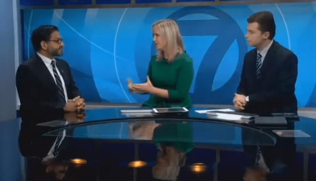 2 men and a woman talking at a news desk with blue background