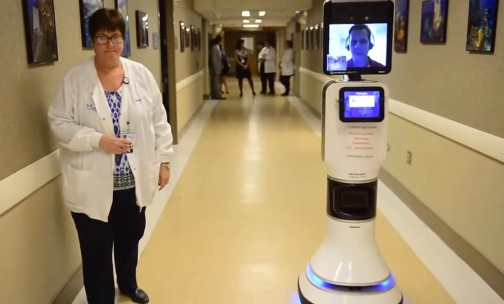 medical employee in hallway next to machine with doctor on screen